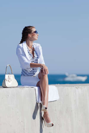 Young woman in white at the sea  Attractive woman in white sits on concrete pier looking away photo