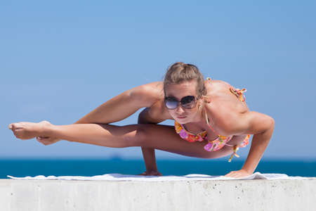 Young woman in bikini at the sea  Attractive woman in swimwear doing yoga at the sea photo
