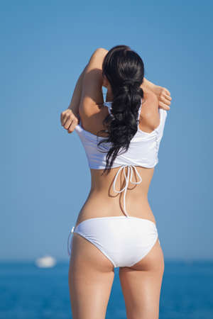 undressing woman: Girl at the sea  Attractive brunette in white swimwear undressing on the beach with his back to the camera