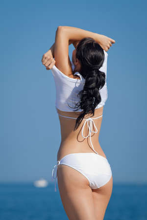 Girl at the sea  Attractive brunette in white swimwear undressing on the beach with his back to the camera photo