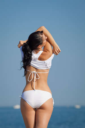 Girl at the sea  Attractive brunette in white swimwear undressing on the beach with his back to the camera