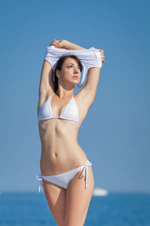 undressing woman: Girl at the sea  Attractive brunette in white swimwear undressing on the beach Stock Photo