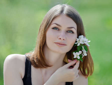 colleen: Portrait of attractive young woman on open air  Girl posing with flower of apple  outdoors