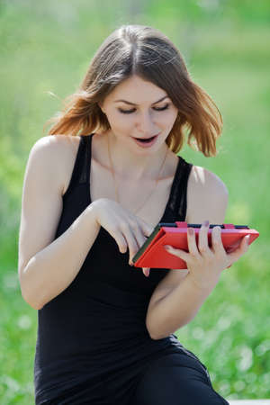 Attractive young woman in the park  Girl uses touchpad on open air photo