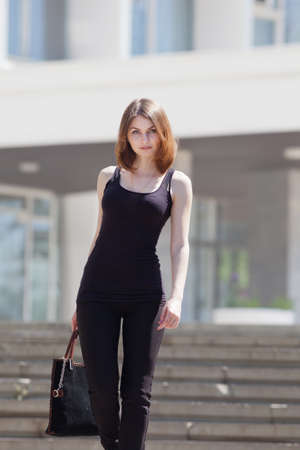 Portrait of attractive young woman outdoors  Slender girl with black bag walking on the stairs