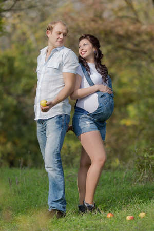 Young man with his pregnant wife on open air photo