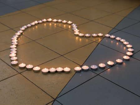 Wedding ceremony  Heart Shape of lit candles on the floor Фото со стока