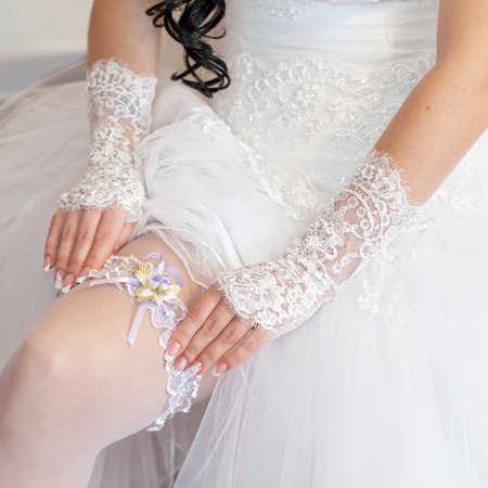 Trouwdag ogenblik Bruid corrigeert kouseband op haar been Stockfoto
