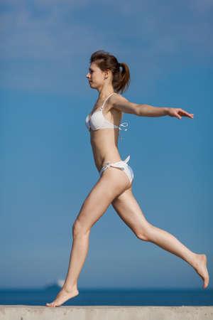 Jogging  Barefoot slim girl in white bikini running along the beach photo