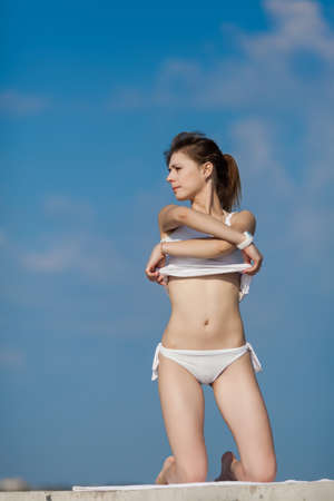 girl undressing: Girl at the sea  Slim girl undressing against of sky looking away