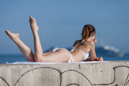 Girl at the sea  Slim girl lying down observing cruise liner photo