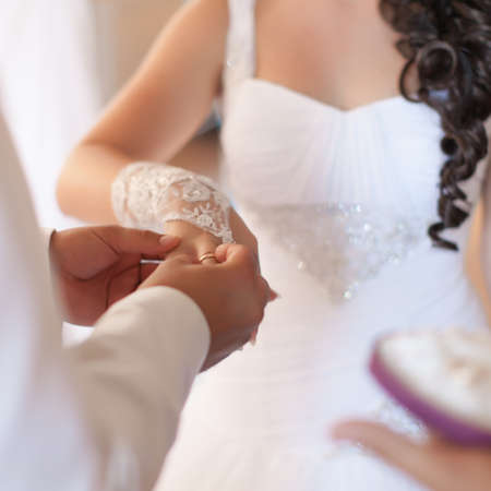 Wedding hands  Groom putting a ring on bride photo