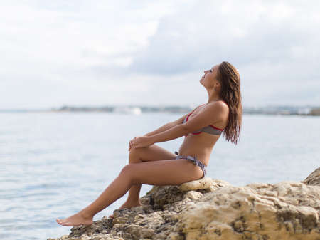 non moving activity: Girl at the sea  Young woman in bikini sitting on rock in sea