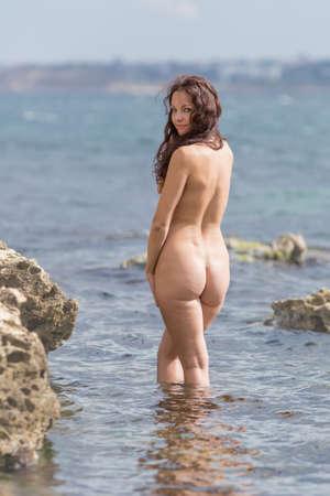 Mujer joven desnuda pose en el mar