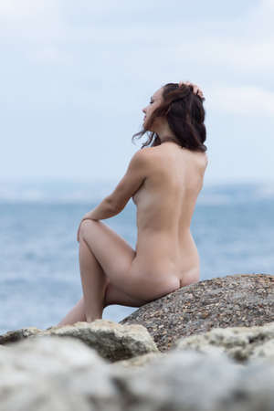 nude young woman: Nude young woman sitting on seashore in cloudy day