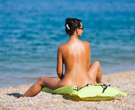 Girl at the sea  Naked young woman sits on swimming mattress on pebble Stock Photo