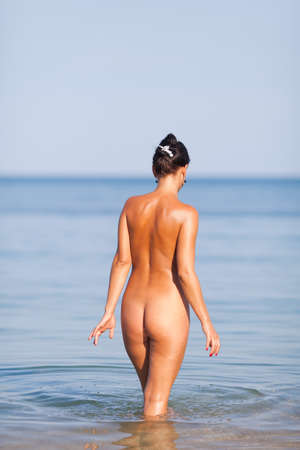 Girl at the sea  Naked young woman going into the sea