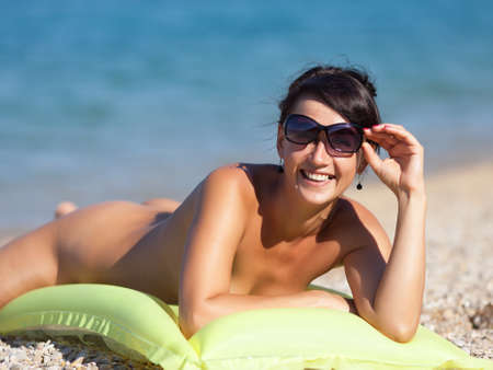 Nude young woman lying on swimming mattress looking at camera through sunglasses Archivio Fotografico