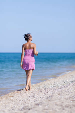 Girl at the sea  Young woman in sundress walks along the seashore photo