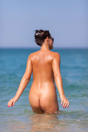 Girl at the sea  Naked young woman going into the sea photo