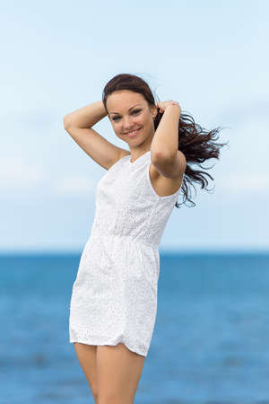 Girl at the sea  Young woman in white adjusting own hair looking at camera smiling photo