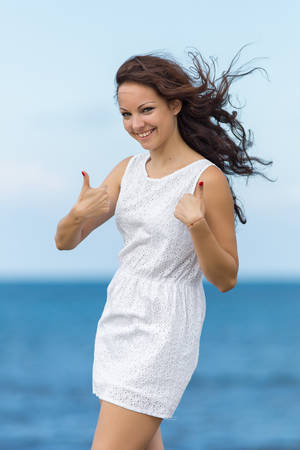 Young woman at the sea  Curly girl in white showing thumbs up looking at camera smiling photo