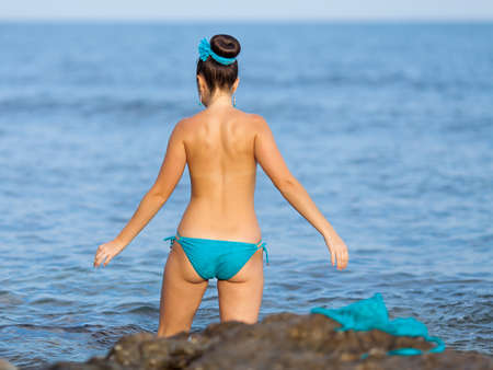 Girl at the sea  Young woman in the sea, rear view  photo