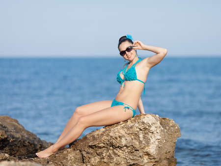 non moving activity: Girl at the sea  Young woman in swimwear sitting on rocky seashore looking at camera smiling