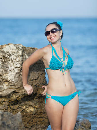 Girl at the sea  Young woman in sunglasses on rocky seashore looking at camera smiling