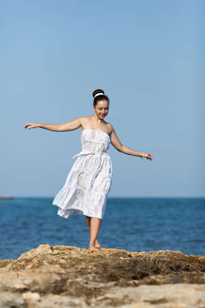 Girl at the sea  Barefoot young woman in white walks on rocky seashore photo