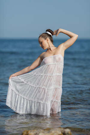 Girl at the sea  Dressed young woman in the sea