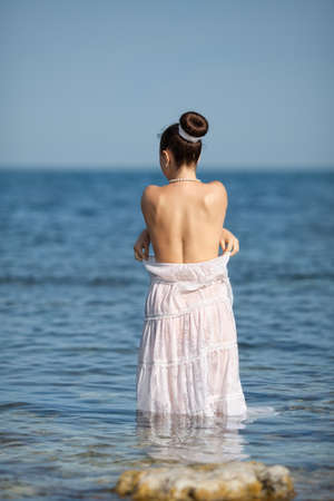 femme se deshabille: Fille � la mer humide jeune femme d�shabill�e dans la mer, vue arri�re