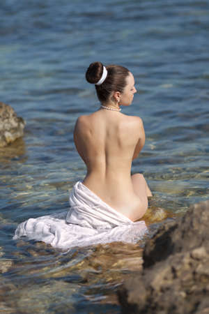 Girl at the sea  Naked young woman in the sea, rear view  photo