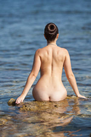 Girl at the sea  Naked young woman in the sea, rear view  Stock Photo