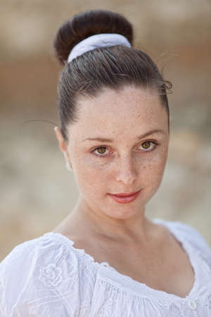 eastern european ethnicity: Portrait of girl outdoors  Young woman with freckles in white dress looking at camera