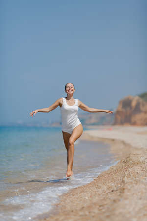 Girl at the sea  Barefoot young woman in white running on seashore photo