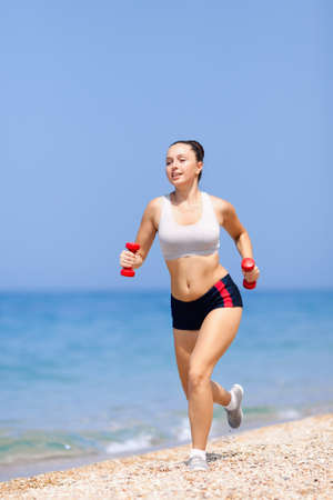 Girl at the sea  Young woman in summer sportwear running along pebble beach  photo
