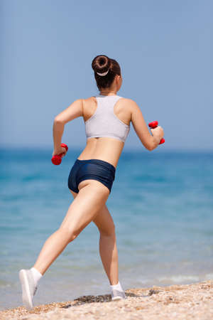 Girl at the sea  Young woman in summer sportwear running along pebble beach, rear view  photo