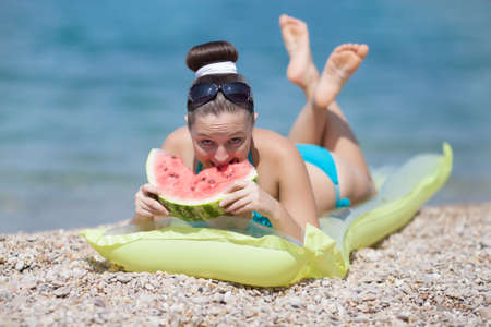 Girl at the sea  Young woman eats watermelon on seashore photo