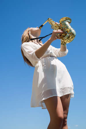 foreshortening: Musician against the sky. Girl playing on saxophone on open air