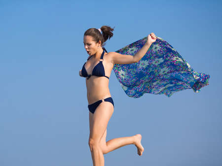 eastern european ethnicity: Girl in bikini on open air. Young woman with pareo runs against the sky