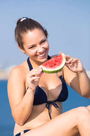 Girl at the sea. Young woman eats watermelon on seashore photo