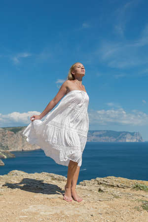 foreshortening: Girl in white sundress on seashore. Young woman posing on against the sky