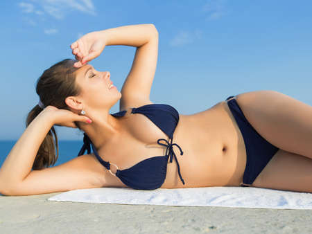 Brunette at the sea. Attractive young woman in dark swimwear lying down on side looking up photo