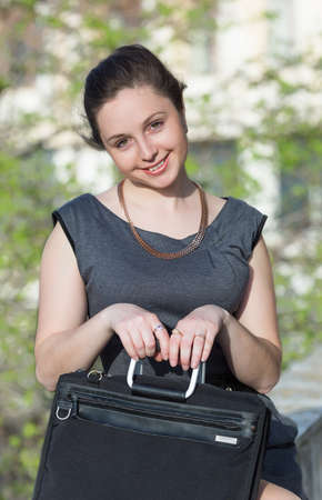 eastern european ethnicity: Young business woman outdoors. Girl in gray suit with laptop looking at camera smiling Stock Photo