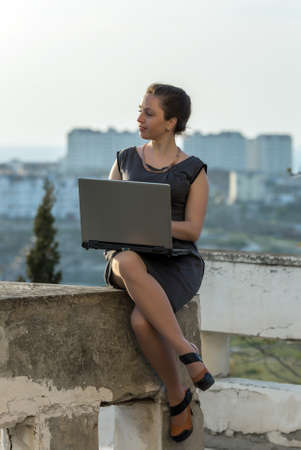 eastern european ethnicity: Young business woman outdoors. Girl with laptop sitting on concrete wall looking away