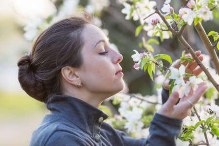 eastern european ethnicity: Young woman outdoors. Attractive girl in gray suit sniffing blossom of apple tree