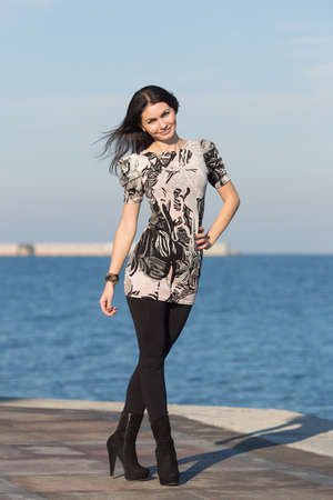 eastern european ethnicity: Attractive woman in black trousers on open air along seafront Stock Photo