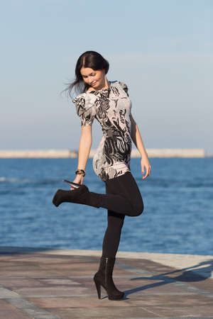 russian ethnicity caucasian: Attractive woman in black leggings on seafront adjusting shoe