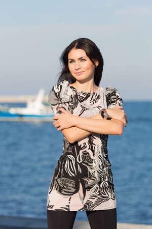 mains crois�es: Attractive femme posant sur les mains bord de mer a travers� sur sa poitrine regarde au loin Banque d'images
